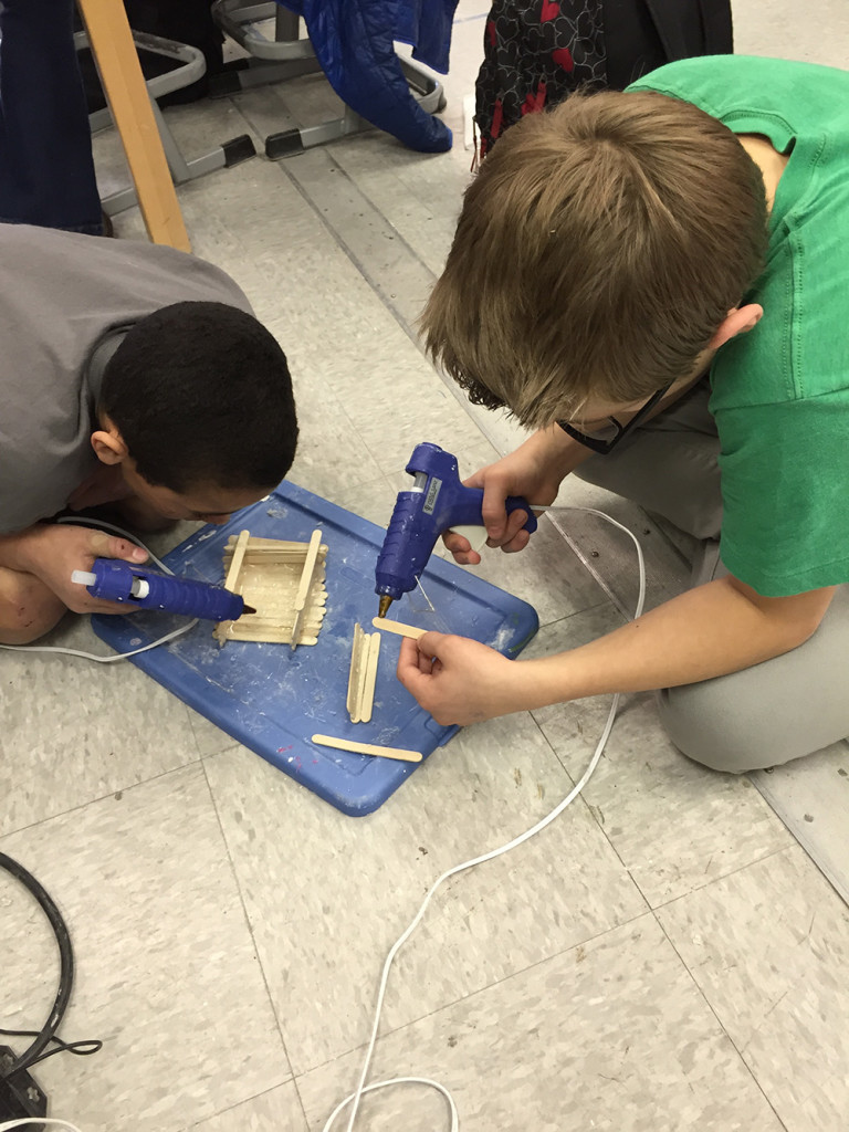 male students building with popsicle sticks
